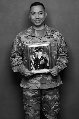 Army Capt. Joseph Quenga stands with a photo