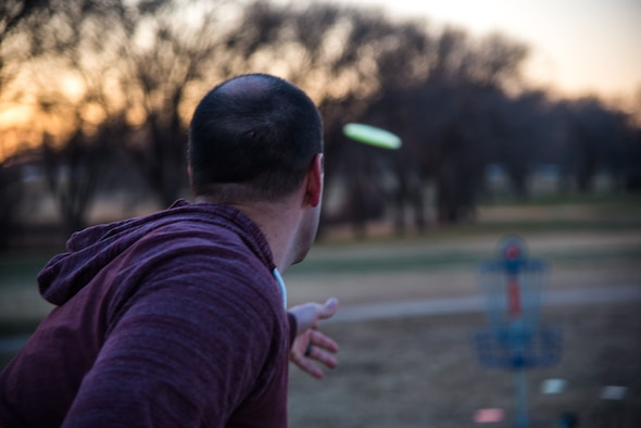 Staff Sgt. Michael Washburn, 27th Special Operations Wing Public Affairs photojournalist, throws a disc on the recently opened disc golf course at Cannon Air Force Base, N.M., on Dec. 13, 2017. The course has nine holes of varying distance, ranging from 100 to 250 meters. (U.S. Air Force photo by Airman 1st Class Vernon Walter)