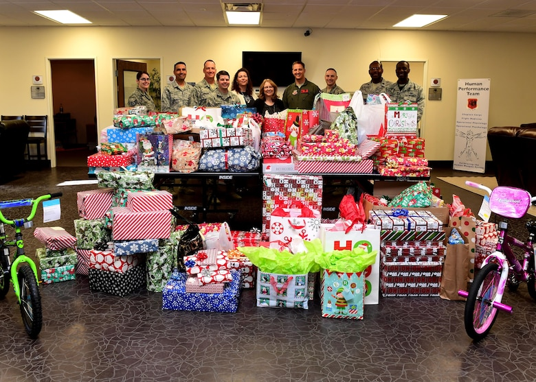 Col. Julian Cheater, 432nd Wing/432nd Air Expeditionary Wing commander, Chief Master Sgt. Jaime Auger, 432nd WG/432nd AEW command chief, and members of the Creech Human Performance Team, presented holiday gifts to representatives from Indian Springs, Dec. 18, 2017, at Creech Air Force Base, Nev. The donated gifts go to aid more than 30 families living below the poverty line. (U.S. Air Force photo/Senior Airman Christian Clausen)