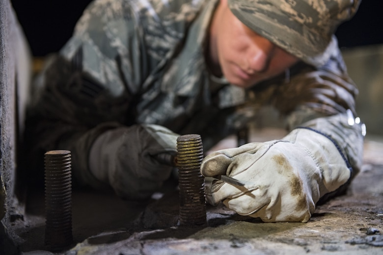 Senior Airman Matthew Melton, 23d Civil Engineer Squadron power production journeyman, clears the threads on a bolt, Nov. 15, 2017, at Moody Air Force Base, Ga. The bolts will hold a fairlead beam in place which is a part of a BAK-12 arresting system that is used on the runway to slow down fighter aircraft in emergency situations. (U.S. Air Force photo by Senior Airman Janiqua P. Robinson)