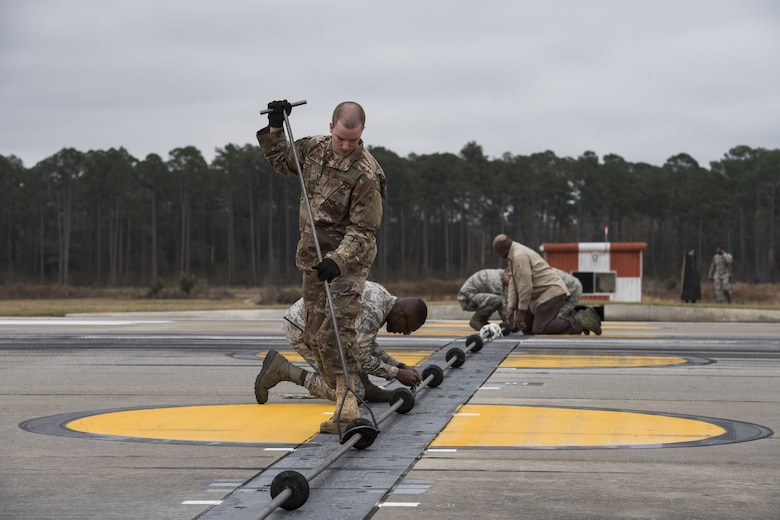Airmen from 23d Civil Engineer Squadron power production shop, work on various tasks while preparing an arresting system for use, Dec. 19, 2017, at Moody Air Force Base, Ga. The beam is a part of a BAK-12 arresting system that is used on the runway to slow down fighter aircraft in emergency situations. (U.S. Air Force photo by Senior Airman Janiqua P. Robinson)