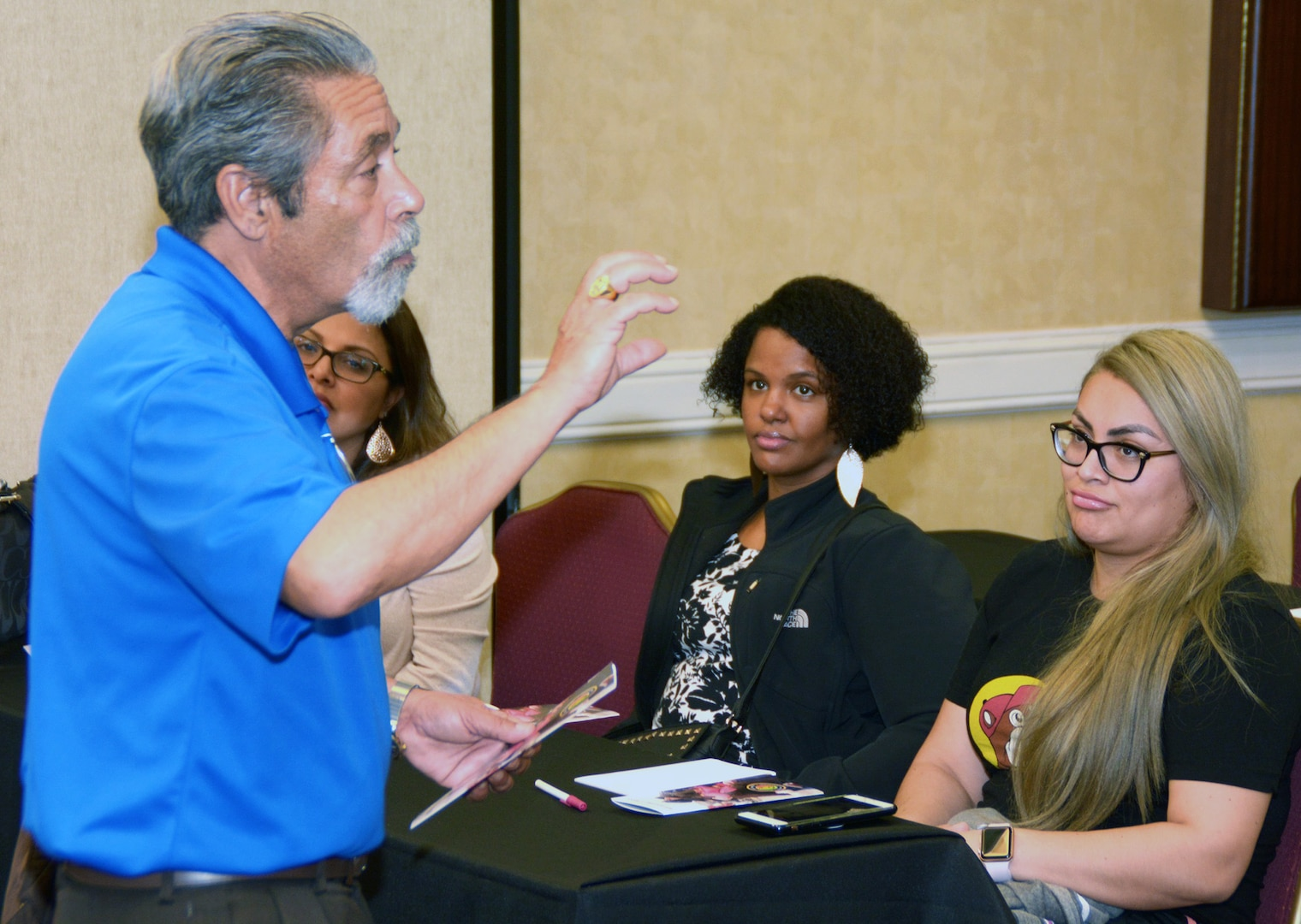 Navy veteran Robert Searles, a facilitator assigned to the Navy's 21st Century Sailor office in Norfolk, Va., speaks with spouses of Navy Recruiting District San Antonio about Operational Stress Control during a district training meeting held at the Crowne Plaza Hotel in Austin Dec. 19. More than 250 recruiters, support personnel and their spouses attended the training where they were provided with support networks, programs, resources, training, and skills needed to overcome adversity and thrive.