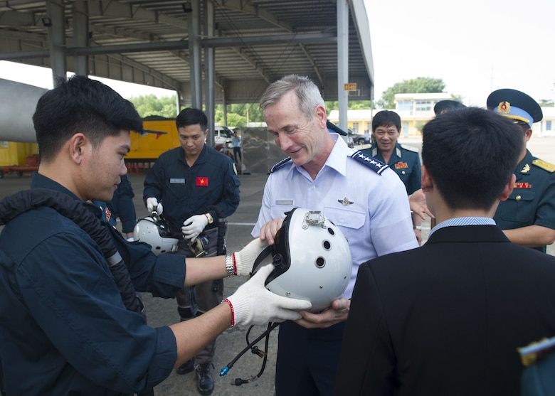 Gen. Terrence J. O'Shaughnessy, Pacific Air Forces commander, inspects a Vietnamese Air Defense-Air Force (ADAF) pilot's helmet, during a visit to Bien Hoa Air Base, Vietnam, Dec. 16.