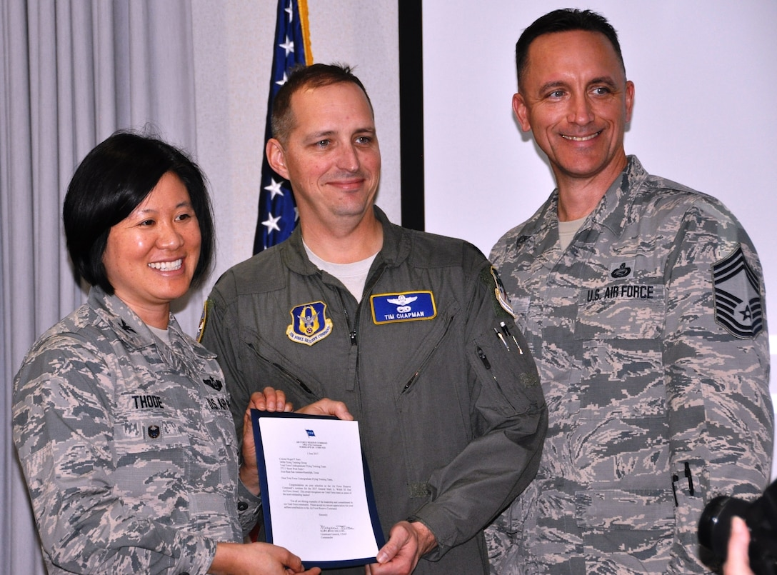 Col. Janette Thode, 340th FTG commander, and superintendent Chief Master Sgt. Jimmie Morris present the Air Force Reserve Command Gen. Mark Welsh One Air Force and Chief of Staff Team Excellence awards went to Undergraduate Flying Training program manager Lt. Col. Timothy Chapman during the December 2017 mandatory unit training assembly. (U.S. Air Force photo)