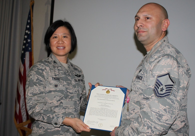 Col Janette Thode, 340th Flying Training Group commander, presents the Meritorious Service Medal to 340th FTG assistant force development NCOIC Master Sgt. Edwardo Morales. (U.S. Air Force photo)