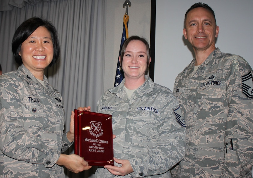 Col. Janette Thode, 340th FTG commander, and superintendent Chief Master Sgt. Jimmie Morris present the second quarter Senior NCO of the Quarter award to Master Sergeant Sarah Cornelius, information technology superintendent, during the December 2017 mandatory unit training assembly. (U.S. Air Force photo)