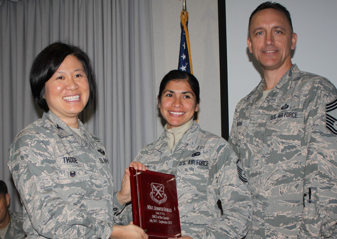 Col. Janette Thode, 340th FTG commander, and superintendent Chief Master Sgt. Jimmie Morris present the third quarter Senior NCO of the Quarter award to Master Sergeant Jennifer Robles, health services section chief, during the December 2017 mandatory unit training assembly. (U.S. Air Force photo)