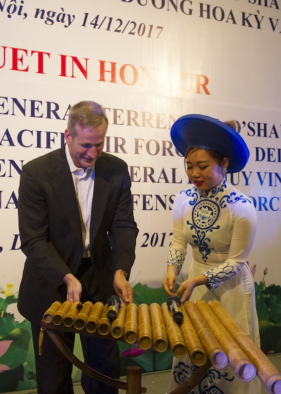Gen. Terrence J. O'Shaughnessy, Pacific Air Forces commander, is instructed on how to play a traditional instrument by a Vietnamese Air Defense-Air Force (ADAF) musician, during a dinner hosted by the ADAF, Hanoi, Vietnam, Dec. 14
