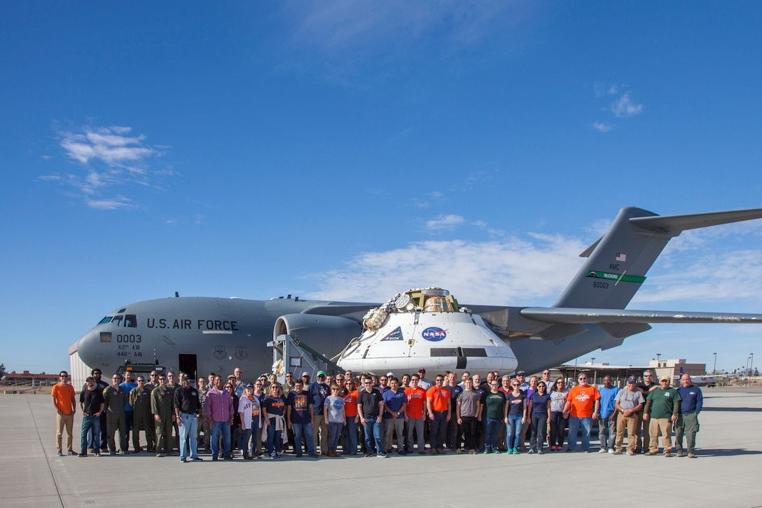 The Orion spacecraft Capsule Parachute Assembly System team pose for a photo before the mockup spacecraft is loaded onto a C-17 Globemaster III, Dec. 11, in Yuma, Arizona. (U.S. Air Force photo by Christopher A. Okula)
