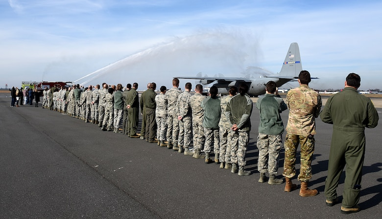 Spectators watch a ceremonious final flight wash as the last C-130 Hercules aircraft attached to the North Carolina Air National Guard Base, Charlotte Douglas International Airport departs for a new assignment at the 165th Airlift Wing in Savannah, Georgia, Dec. 18, 2017. The NCANG is in transition from flying the C-130 Hercules to C-17 Globemaster III aircraft. The change in mission will require not only a transition in aircraft and personnel, but an increase in structures throughout the base.
