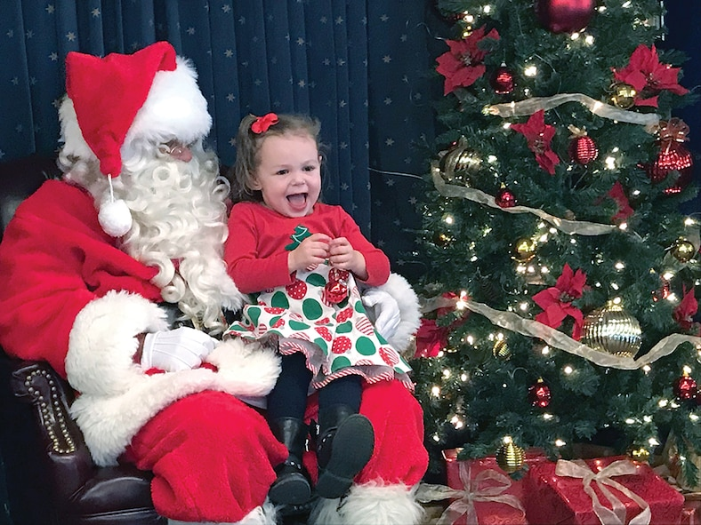 Three-year-old Ruby Mills greets Santa during Saturday morning's Hearts Apart Kids' Holiday Party held at the Mountain View Club. More than 100 people attended this year's event, including Col. Richard W. Gibbs, 377th Air Base Wing commander.