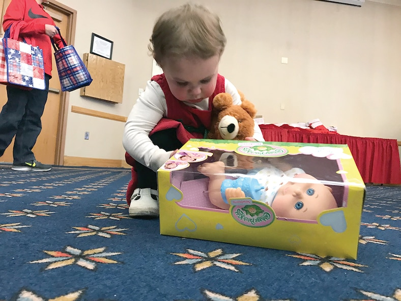 Zoey Mills, 2, opens her present from Santa. She also celebrated her birthday Dec. 16 during the Hearts Apart Kids' Christmas Party. More than 100 people attended this year's event.