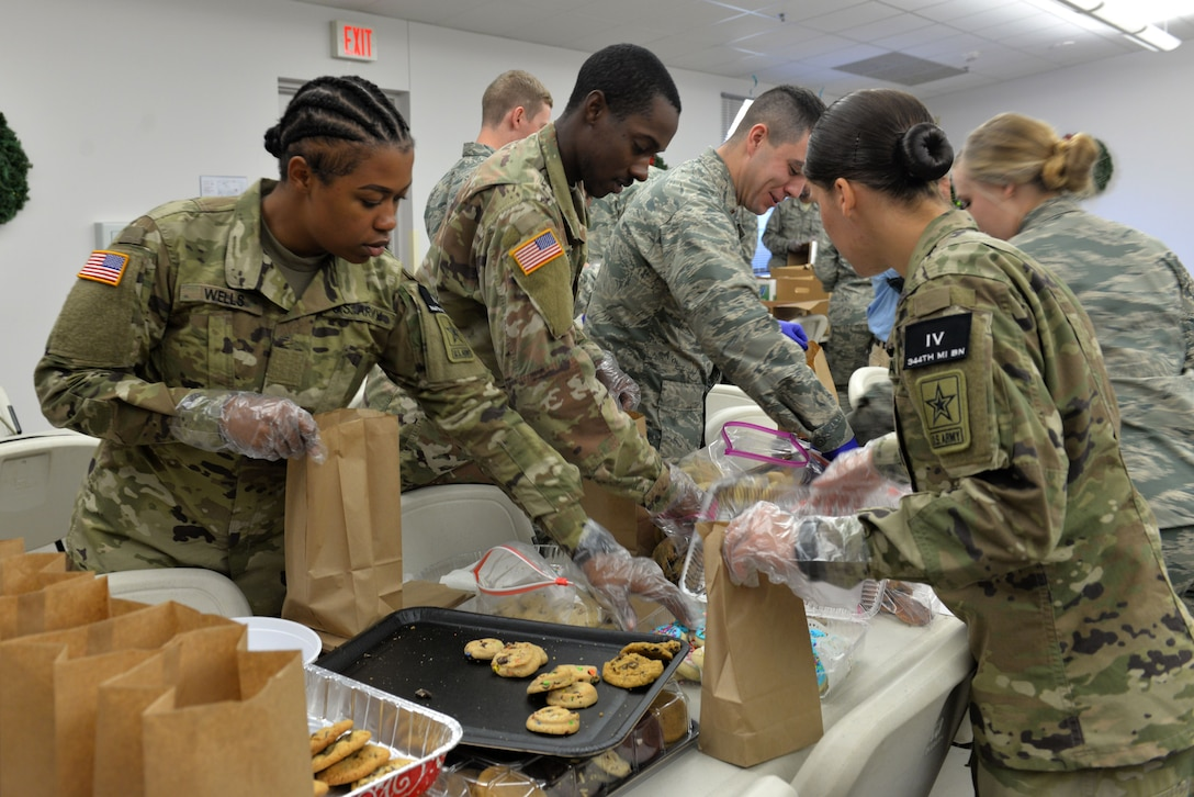 U. S. Army Pvt. Kiara Wells, 344th Military Intelligence Battalion trainee and Pvt. John Tracy, 344th MIBN trainee, prepare bags of cookies at the Taylor Chapel on Goodfellow Air Force Base, Texas, for distribution to Goodfellow trainees Dec. 20, 2017. Over 40 volunteers gathered at the Taylor Chapel to provide some holiday cheer by filling bags full of cookies for Goodfellow Airmen before they leave for the holidays.