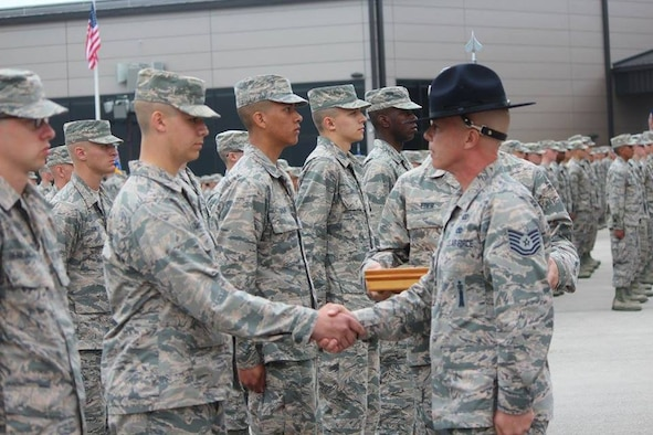 Tech. Sgt. James MacKay (currently Master Sergeant) presents the Airman's Coin to a graduating Airman in his flight during graduation ceremonies. MacKay led 13 flights during his time as a MTI. The Airman's Coin Ceremony represents the culmination of 7 1/2 weeks of Basic Military Training. The coveted Airman's Coin is given to each graduating Airman. (U.S. Air Force photo).