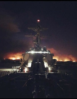 USS Sterett (DDG 104) moores in Port Hueneme as the Ventura County hills endure rampant fires, Dec. 5. The destroyer visited Naval Surface Warfare Center, Port Hueneme Division for a combat systems assessment and groom.