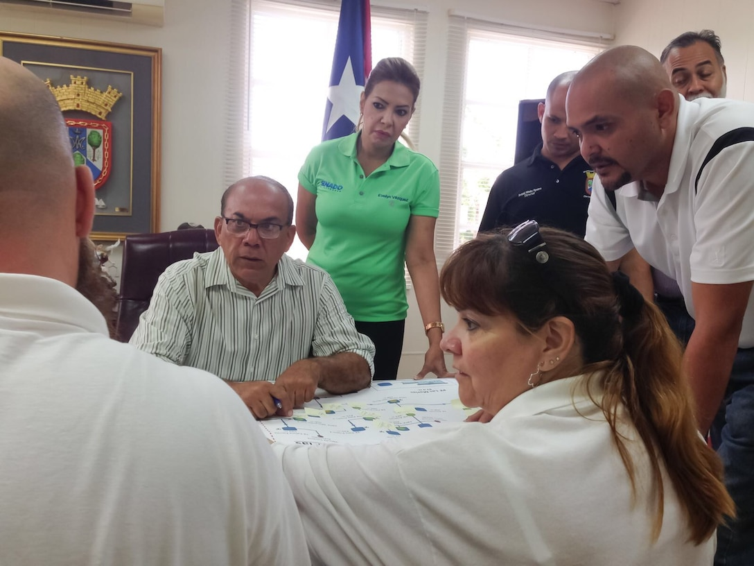 Sandra Eudy (center), an Emergency Management Specialist with South Pacific Division, talks with members of the Puerto Rican government. Hurricane Maria struck Puerto Rico and the U.S. Virgin Islands in mid-Sept.