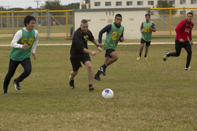 MCAS FUTENMA, OKINAWA, Japan— Chief Petty Officer Michael Garcia races a Kokusai University Student to the ball during a soccer game Dec. 17 on Marine Corps Air Station Futenma, Okinawa, Japan.
