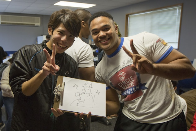 MCAS FUTENMA, OKINAWA, Japan— Nozomu Miyagi, left, and Lance Cpl. Malik Miller pose with their drawing after a game of Pictionary in the Single Marine Program building Dec. 17 on Marine Corps Air Station Futenma, Okinawa, Japan.