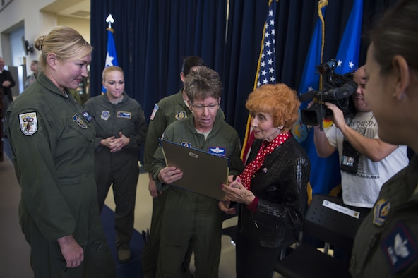 Ms. Elinor Otto autographs pictures for the members of March Air Reserve Base.