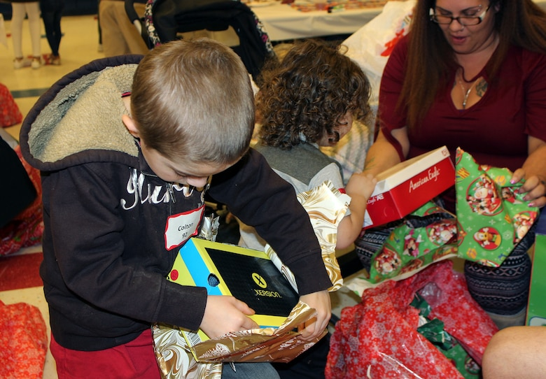 "Air Force Civil Engineeer Center volunteers distributed gifts to 165 children at the ""Spread the Joy"" gift-giving party and dinner held at Lucille Moore Elementary School in Panama City on December 15. Each child received a coat, shirt, pants, a pair of shoes and two toys of their choice. Santa stopped by to with everyone a Merry Christmas."