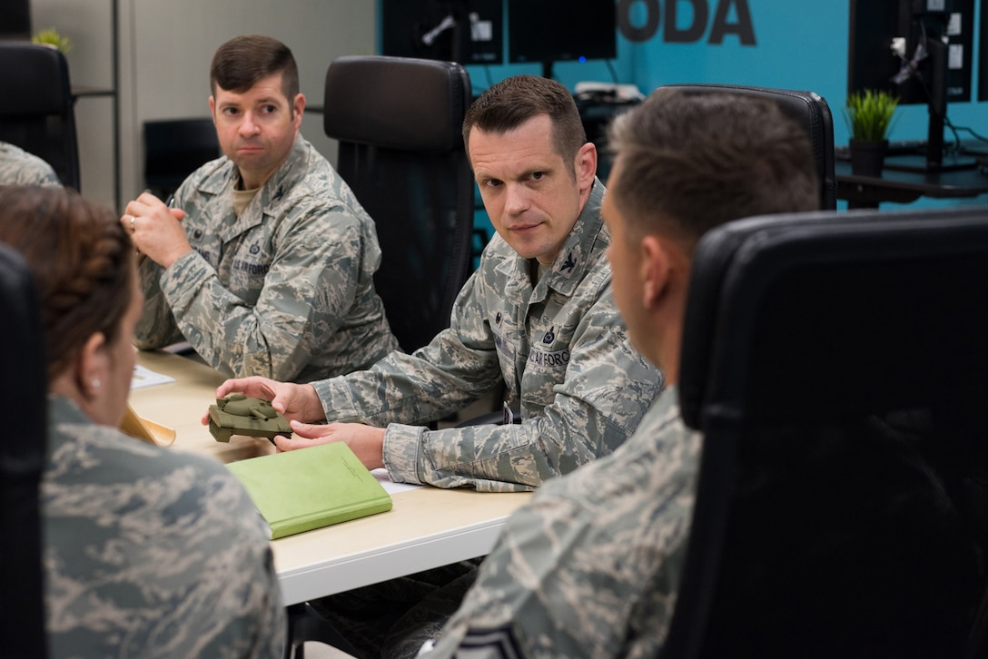 Col. Jason M. Brown (center), 480th Intelligence, Surveillance and Reconnaissance Wing commander, holds a 3D-printed tank.
