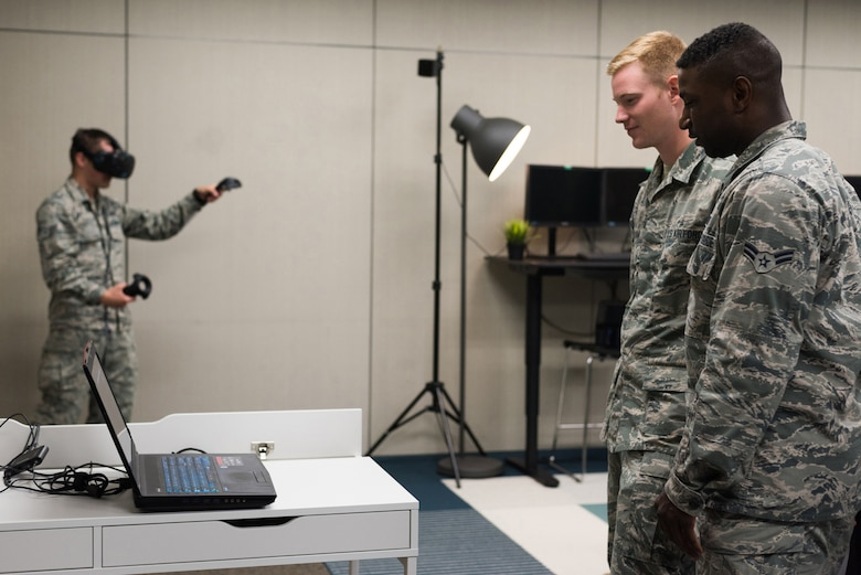 Airman 1st Class Mark (left), 13th Intelligence Squadron geospatial imagery analyst, uses Tilt Brush, a virtual reality program, to draw and paint in the innovation lab as Airman 1st Class Justin and Airman 1st Class Charles, 13 IS geospatial imagery analysts, view his creation at Beale Air Force Base, Calif., July 26, 2017.
