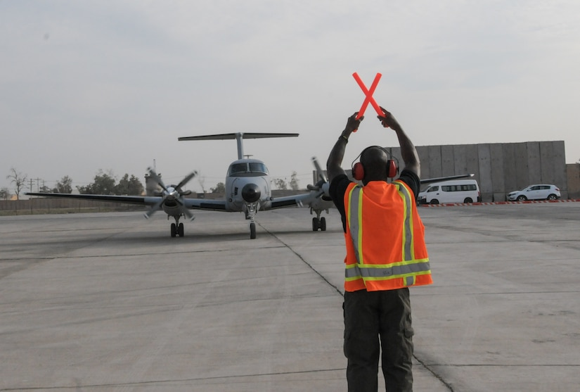 Air traffic controller guides a plane on the ground.