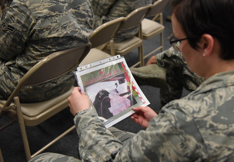 Capt. Rachel Donoho, 81st Communications Squadron operations flight commander, looks at a past DUI accident slide during an alcohol awareness briefing at the 81st CS Dec. 19, 2017, on Keesler Air Force Base, Mississippi. December is Impaired Driving Awareness Month. More than 200 people were killed in Mississippi last year in drunk driving related incidents. (U.S. Air Force photo by Kemberly Groue)