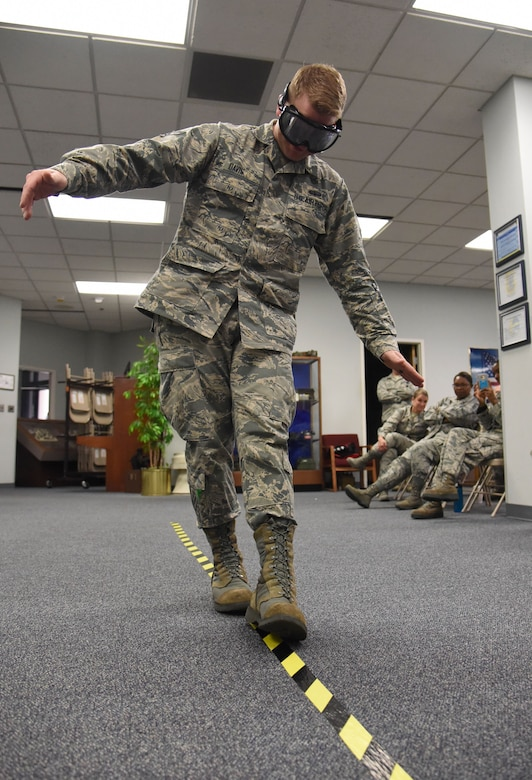 Airman 1st Class Larry Davis, 81st Communications Squadron client systems technician, is subjected to a field sobriety test while wearing drunk goggles during an alcohol awareness briefing at the 81st CS Dec. 19, 2017, on Keesler Air Force Base, Mississippi. December is Impaired Driving Awareness Month. More than 200 people were killed in Mississippi last year in drunk driving related incidents. (U.S. Air Force photo by Kemberly Groue)