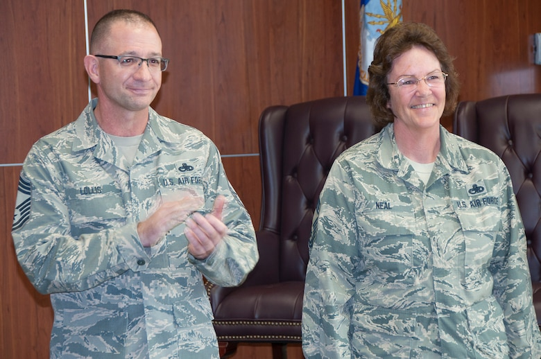 Chief Master Sgts. Marion Lollis Jr., 919th Special Operations Aircraft Maintenance Squadron,  and Jennifer Neal, 919th Special Operations Maintenance Group react to applause