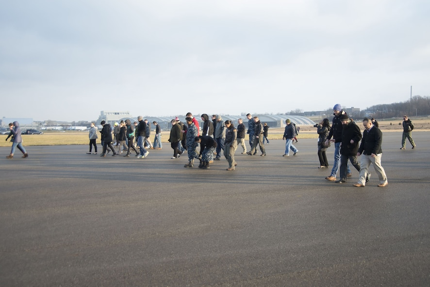 Members of Naval Medical Research Unit-Dayton conduct a foreign-object-damage walk-down Dec. 19, 2017, on the Wright-Patterson Air Force Base, Ohio, Area B flight line in advance of the arrival of a Marine Corps MV-22 Osprey aircraft. The unit was preparing the seldom-used runway near the National Museum of the Air Force for the arrival the plane that was signed over to the unit for medical research. (U.S. Air Force photo by R.J. Oriez)