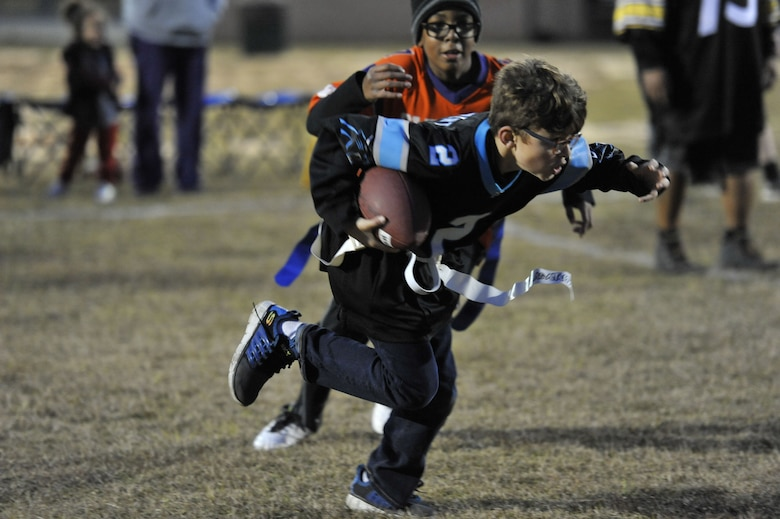 Andre, left, Weapons Station youth center participant, attempts to stop Everett, WS youth center participant, from making a touchdown Dec. 14, 2017, at Joint Base Charleston – Weapons Station, S.C.