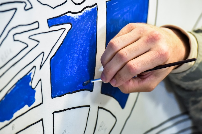 A 628th Logistics Readiness Squadron vehicle operator paints a drawing of a vehicle operator occupational badge at the vehicle operations building on Joint Base Charleston, S.C., Dec. 9, 2017.