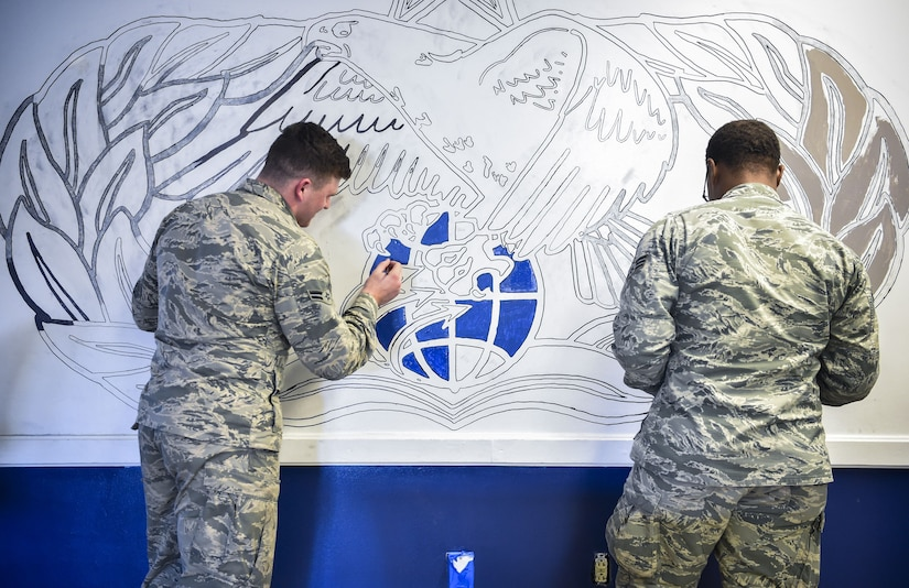Vehicle operators from the 628th Logistics Readiness Squadron paint an occupational badge at the vehicle operations building on Joint Base Charleston, S.C., Dec. 9, 2017.