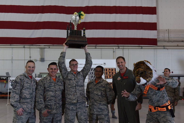 Col. Julian Cheater, 432nd Wing/Air Expeditionary Wing commander, and Chief Master Sgt. Jamie Auger, 432nd WG/AEW command chief, stand with the winners of the 432nd Aircraft Maintenance Squadron load crew of the quarter competition Dec. 8, 2017, at Creech Air Force Base, Nev. This quarter, participants wore full chemical suits while performing the mandatory tasks for their aircraft during the competition. (U.S. Air Force photo by Airman 1st Class Haley Stevens)