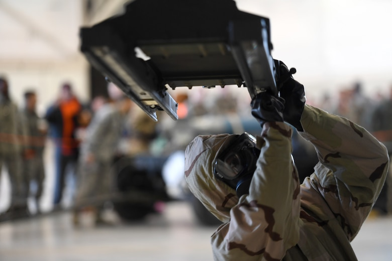 An Airman assigned to the 432nd Aircraft Maintenance Squadron Tiger Aircraft Maintenance Unit prepares to load a GBU-38 Joint Direct Attack Munition during a weapons load competition Dec. 8, 2017, at Creech Air Force Base, Nev. This was the first weapons load that required participants to wear full chemical, biological, radiological, nuclear and explosives gear in more than three years. (U.S. Air Force photo by Senior Airman James Thompson)