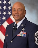 Official photo for Chief MSgt. Anthony B. Duplechain in service dress uniform with U.S. flag in the background.