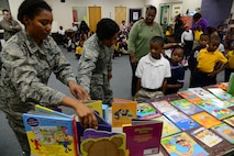 Capt. Alisha Foster, 14th Flying Training Wing Equal Opportunity Director, and Capt. Tara Dixon, 14th FTW Chaplain, help children pick out a book Dec. 20, 2017, at West Lowndes Elementary School in Columbus, Mississippi. Every child got to select a book and the left over books were donated to the school's library. (U.S. Air Force photo by Airman 1st Class Beaux Hebert)
