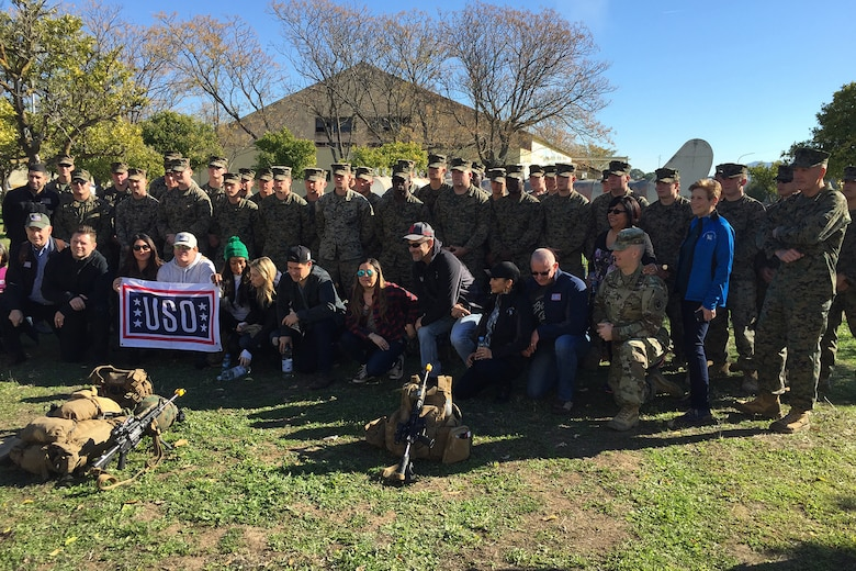 Service members and civilians pose for a photo.