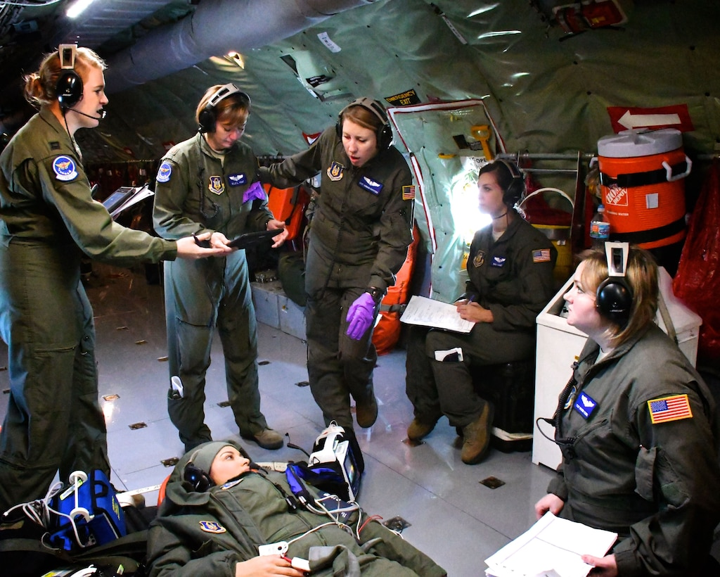 Flight nurses and medical technicians of the 932nd Aeromedical Evacuation Squadron, located at Scott Air Force Base, Ill., discuss over radio headsets how to care for a simulated practice patient during a training flight Dec. 17, 2017.  They flew a scheduled training flight, to get experience in the air, courtesy of the 507th Air Refueling Wing aircrew aboard a KC-135 plane.  This gave them a chance to provide upgrade training and refresher skills to several Airmen, separately from unit training assembly weekends.  The 932nd Airlift Wing is a 22nd Air Force unit, under the Air Force Reserve Command.  (U.S. Air Force photo by Lt. Col. Stan Paregien)