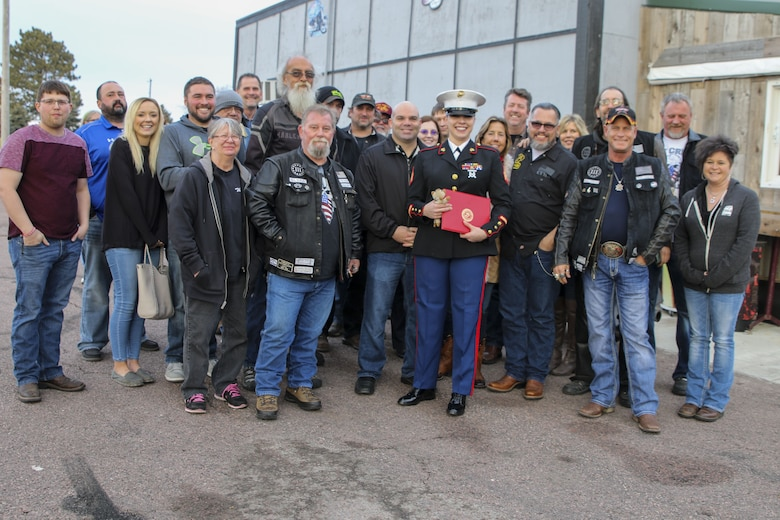 Sergeant Sara McGaffee, a Sioux Falls, S.D., native, poses for a photo with her friends and family after the Marines of Recruiting Sub Station Sioux Falls presented her with the Purple Heart Medal. On Oct. 20th, 2010, while deployed with Combat Logistics Battalion 3, McGaffee's vehicle was hit by an improvised explosive device while conducting convoy operations in support of Operation Steel Dawn II in the Helmand province of Afghanistan. McGaffee was awarded her Purple Heart, Dec. 16, 2017 in Sioux Falls, S.D., in front of a detail of Marines and her local friends and family.