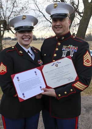 Gunnery Sgt. Paul Odonnell, the staff noncommissioned officer in charge of Marine Corps Recruiting Sub Station Sioux Falls, posed for a photo with Sgt. Sarah McGaffee, a Sioux Falls, S.D., native, after presenting her with the Purple Heart Medal. On Oct. 20th, 2010, while deployed with Combat Logistics Battalion 3, McGaffee's vehicle was hit by an improvised explosive device while conducting convoy operations in support of Operation Steel Dawn II in the Helmand province of Afghanistan. McGaffee was awarded her Purple Heart, Dec. 16, 2017 in Sioux Falls, S.D., in front of a detail of Marines and her local friends and family.