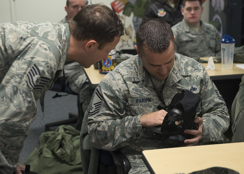 Tech. Sgt. Troy Zimmerman, 366th Civil Engineer Squadron emergency management NCOIC, assists Tech. Sgt. Jason Parvin, 366th Equipment Maintenance Squadron fabrication flight chief, during chemical, biological, radiological, nuclear and explosives training Dec. 20, 2017, at Mountain Home Air Force Base, Idaho. CBRNE training prepares Airmen to survive and work in a harmful environment anywhere in the world. (U.S. Air Force photo by Airman 1st Class JaNae Capuno)
