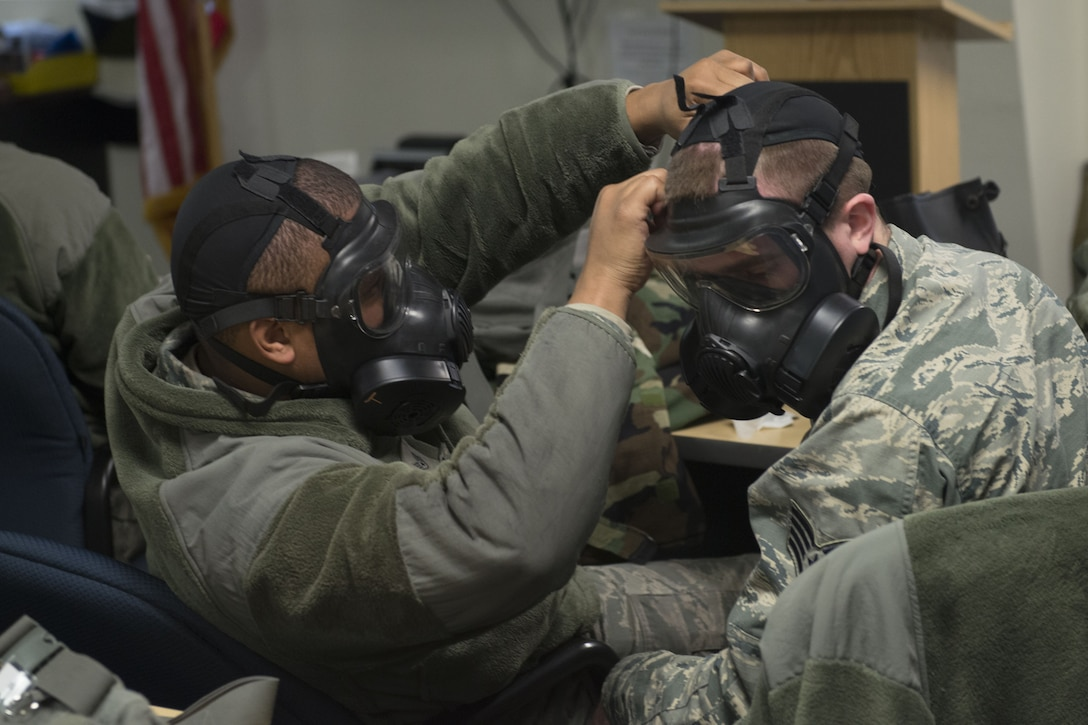 Staff Sgt. Michael Williams, 366th Aircraft Maintenance Squadron weapons load crew team chief, performs a buddy check on Staff Sgt. Anthony Slone, 366th Equipment Maintenance Squadron armament technician Dec. 20, 2017, at Mountain Home Air Force Base, Idaho. CBRNE training prepares Airmen to survive and work in a harmful environment anywhere in the world. (U.S. Air Force photo by Airman 1st Class JaNae Capuno)