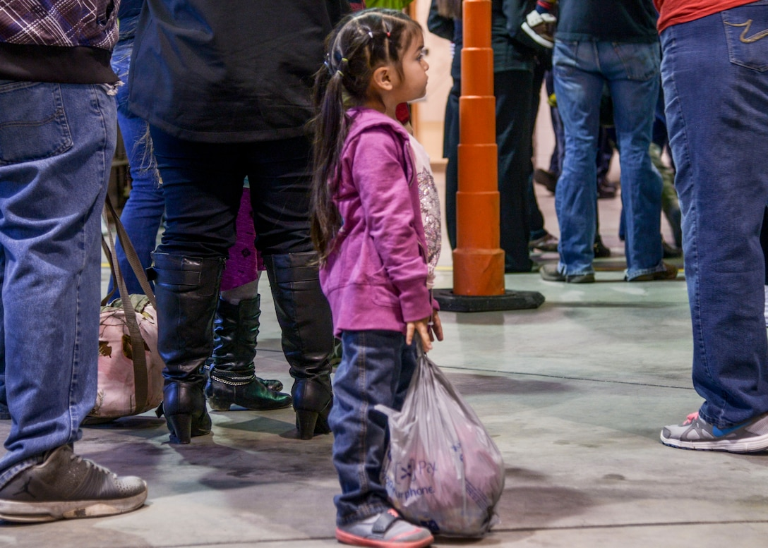 A child waits patiently for dinner at the Operation Holiday Cheer on Dec. 20 at Kirtland Air Force Base, New Mexico. This event is hosted by the Kirtland Fire Department and serves underprivileged families in the local communities by giving them a full holiday meal and a visit with Santa, who sends them home with a gift.