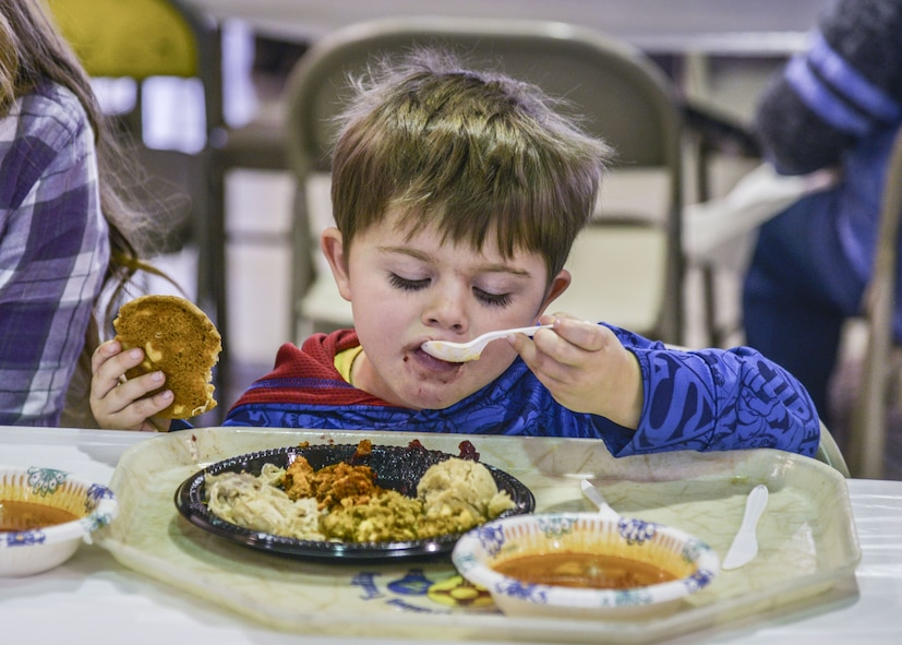 A child eats his holiday meal at the annual Operation Holiday Cheer on Dec. 20 at Kirtland Air Force Base, New Mexico. This event is hosted by the Kirtland Fire Department and serves underprivileged families in the local communities by giving them a full holiday meal and a visit with Santa, who sends them home with a gift.