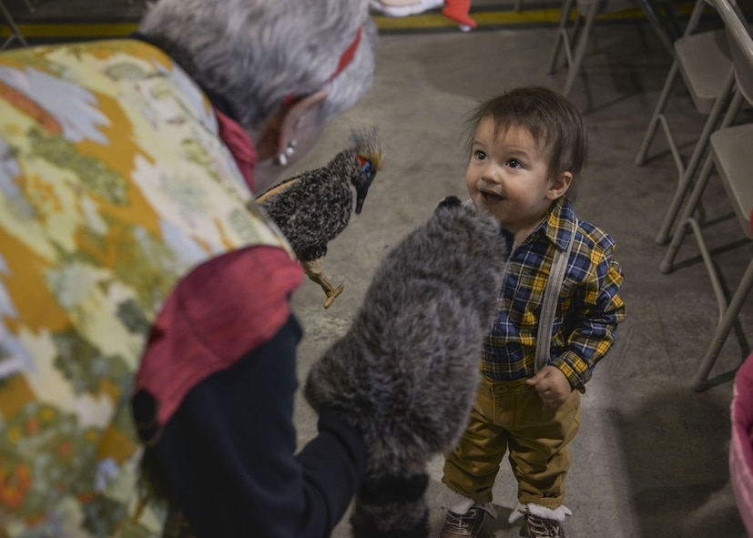A child admires the animals at the Operation Holiday Cheer on Dec. 20 at Kirtland Air Force Base, New Mexico. This event is hosted by the Kirtland Fire Department and serves underprivileged families in the local communities by giving them a full holiday meal and a visit with Santa, who sends them home with a gift.
