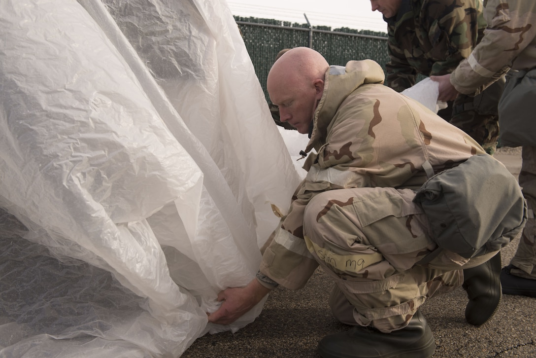 Tech. Sgt. Brian Medley, 366th Equipment Maintenance Squadron metals technology section chief, places a plastic cover over a vehicle during chemical, biological, radiological, nuclear and explosives training Dec. 20, 2017, at Mountain Home Air Force Base, Idaho. CBRNE training prepares Airmen to survive and work in a harmful environment anywhere in the world. (U.S. Air Force photo by Airman 1st Class JaNae Capuno)