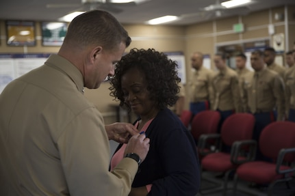 U.S. Marine Corps Col. Terry M. Johnson, Commanding Officer, 12th Marine Corps District, Marine Corps Recruit Depot, San Diego, presents Ms. Gloria Pettis with a Commendation for Meritorious Civilian Service Medal for her 36 years of faithful and dedicated federal service, Dec. 21, 2017. Ms. Pettis served as the Financial Management Analyst for the 12th Marine Corps District for almost 25 years.