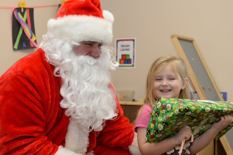 Santa Claus gives a present to a child inside the Youth & Family Services Child Development Center in Rapid City, S.D., Dec. 19, 2017. Ellsworth Airmen have participated in the toy drive for 11 consecutive years. (U.S. Air Force photo by Airman 1st Class Nicolas Z. Erwin)
